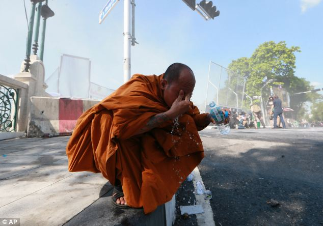 Hurt: A Thai Buddhist monk washes his eyes after riot police fired tear gas at protesters  today