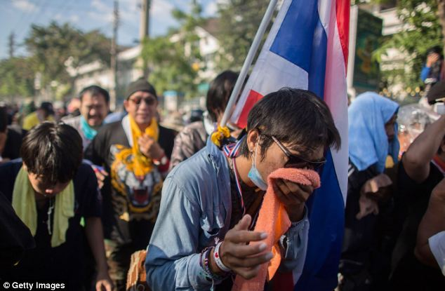 Struggle: Other protestors hold cloths to their noses and mouths as they suffer the effects of the gas cannister