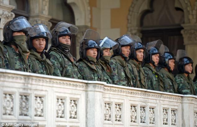 Standing guard: Thai riot police line up at Government House during the violent demonstrations