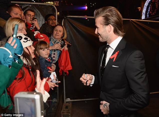 Lucky children: David spent some time signing autographs for the children waiting on the red carpet