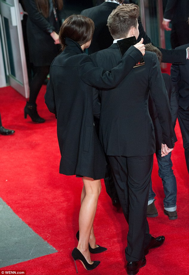 Proud mum: Victoria wrapped a protective arm around eldest son Brooklyn as they made their way inside the venue