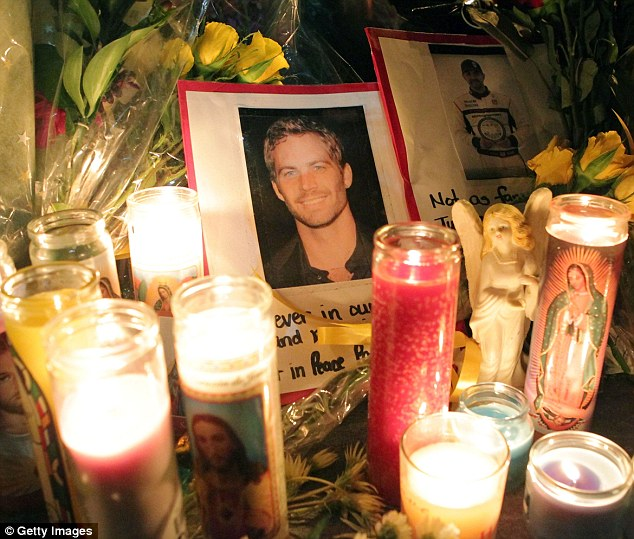 Tribute: Fans placed flowers and cards at the crash site where Paul Walker died on Saturday in Valencia, California