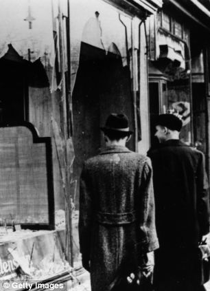 Onlookers take in the destruction in the wake of Kristallnacht, looking through the smashed windows of a Jewish shop following the riots which erupted on November 9, 1938