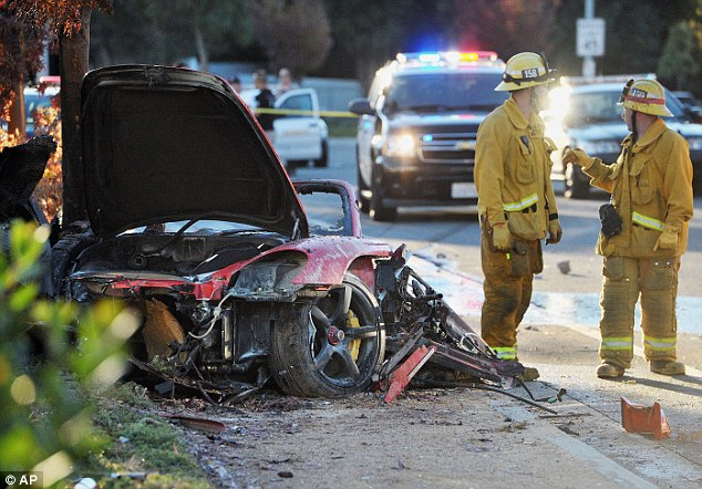 Smash: Sheriff's deputies work near the wreckage of the Porsche in which actor Paul Walker and his friend Roger Rodas were driving on Saturday