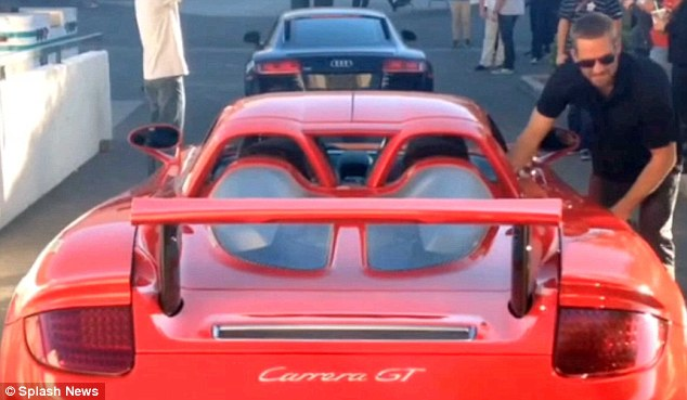 Last picture: Fast & Furious star Paul Walker is pictured by the red Porsche  Carrera GY that he was killed in when it crashed and burst into flames - less than half an hour before the fatal crash