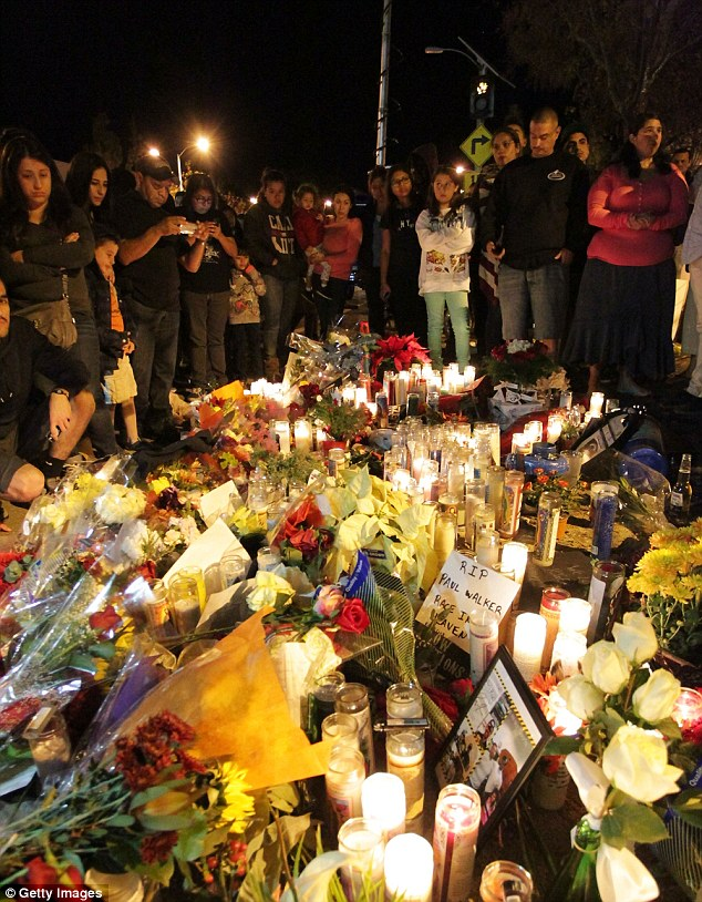 Vigil: Fans congregate to pay respects at a makeshift memorial for Paul Walker at the crash site in Valencia, California