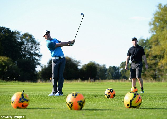 In the swing: Rooney watches McIlroy take a shot