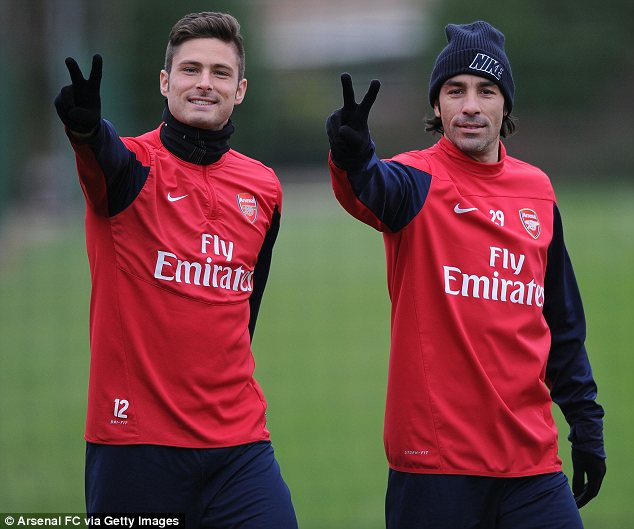 Arsenal's Olivier Giroud and Robert Pires gesture before a training session