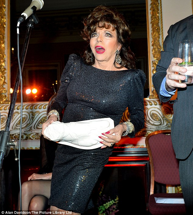 Stylish: Joan attended the event in an embellished black evening dress with distinctive shoulder pads