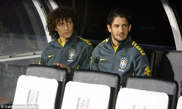 Waiting: Luiz and Alexandre Pato sit on the Brazil bench at Fulham but both will be heavily involved come the summer