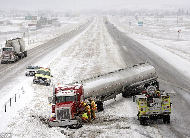 A tanker truck is tended to by firefighters after sliding off the snowy highway near mile marker 48 on Interstate 90 in Piedmont, South Dakota