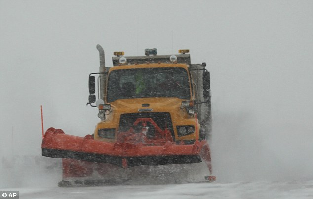 A Department of Transportation plow clears snow from the northbound lane of Highway 85 near Jay Em, Wyoming