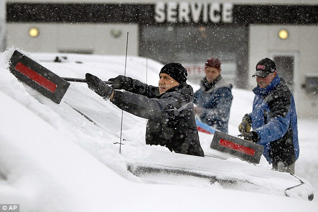 Sam Flaifel, left, Dave Warner, center, and Pat Riestenberg, clear snow from 400 cars in Brooklyn Center, Minnesota today. A wintry storm pushing through the Rockies and Midwest is bringing bitterly cold temperatures and treacherous driving conditions