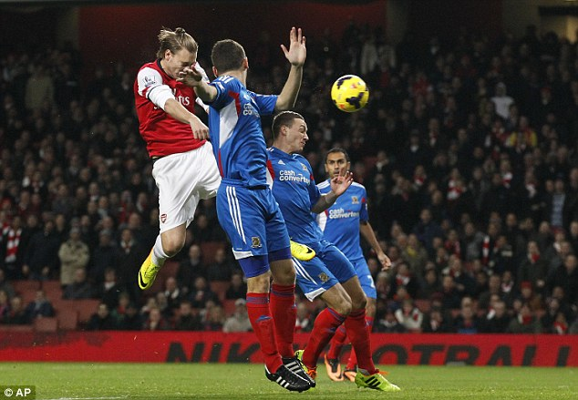 High hopes: Bendtner rises to beat Alex Bruce and James Chester (right) to the ball