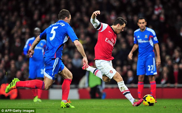 Eyes on the ball: Ozil slots the ball home after latching on to Ramsey's pass