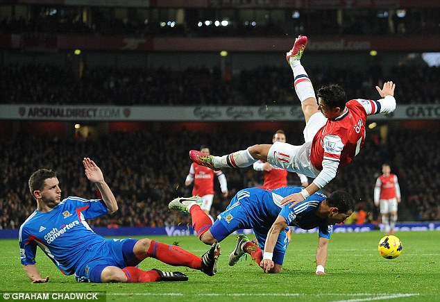 Head over heels: Mesut Ozil is sent flying in the box under pressure from Liam Rosenior (right) and Alex Bruce