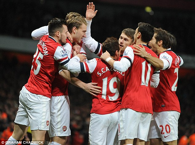 Winning streak: Arsenal players celebrate their first goal of the game during their 2-0 win over Hull