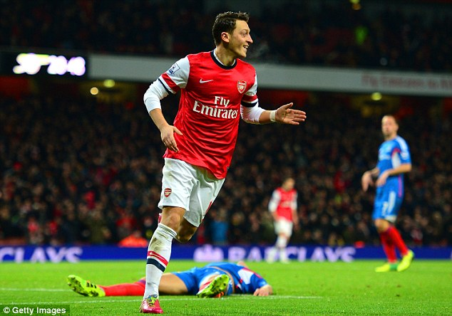 Clear at the top: Mesut Ozil celebrates scoring Arsenal's second goal against Hull at the Emirates