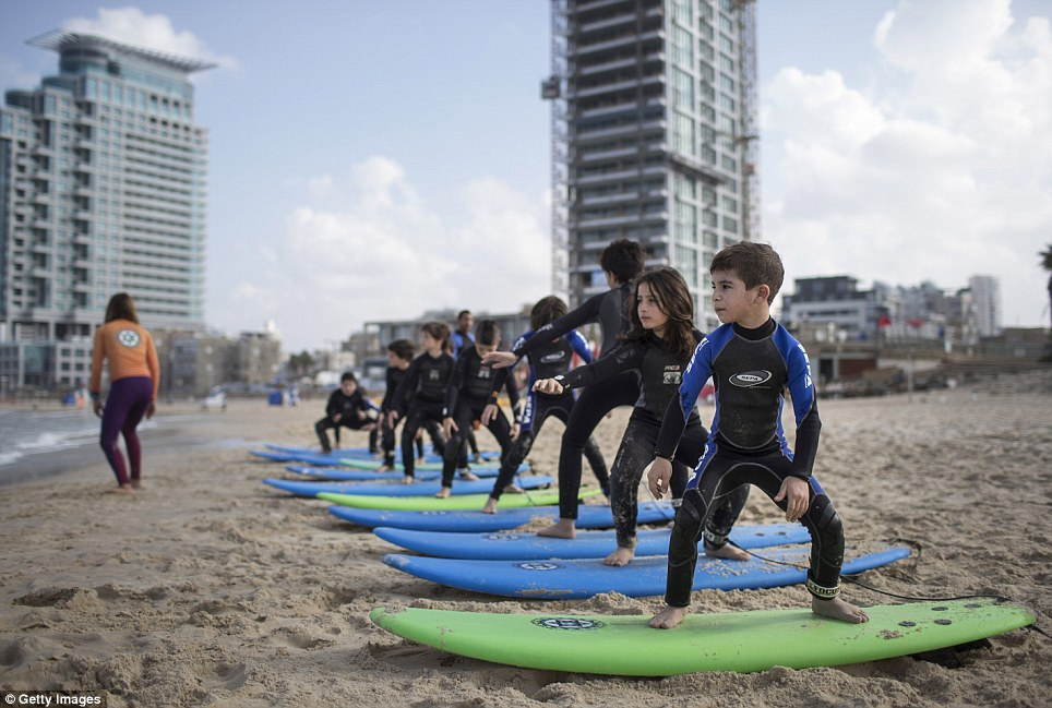 Children practice on the beach as they spend the Jewish holiday of Hanukkah, the festival of light, at the Israeli surf club in Tel Aviv
