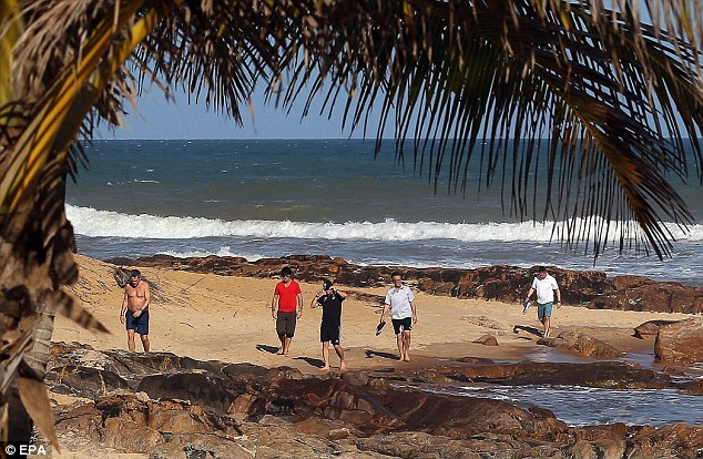 Relaxed mood: German coach Jogi Low (second left) takes time out on the resort beach before learning his country's fate