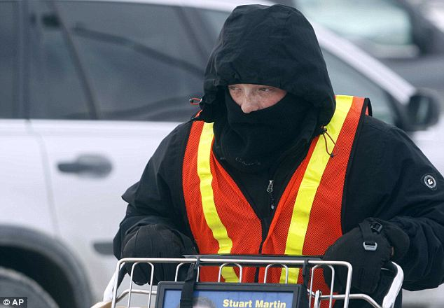 Digging in: Josh Scharf retrieves a shopping cart on a cold afternoon with single-digit temperatures Wednesday in Rapid City, South Dakota