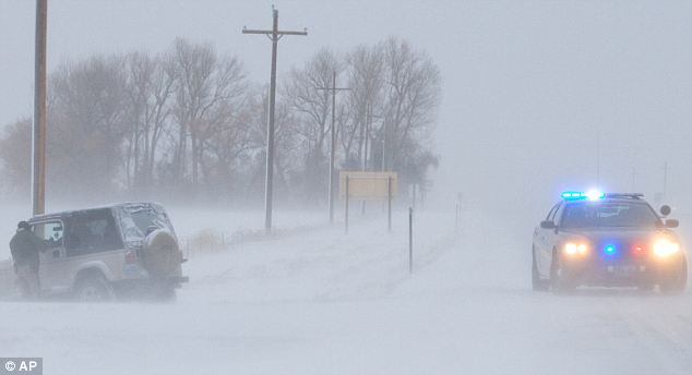 Whiteout conditions; Wyoming Highway Patrol Trooper Blain Mollett investigates a car the went off the road along on U.S. Highway 14-A west of Powell, Wyoming