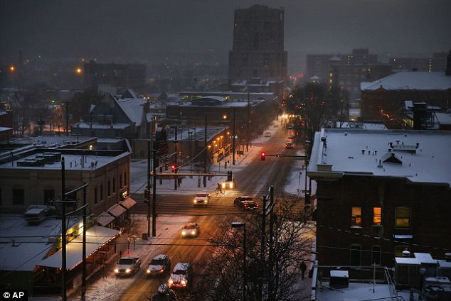 Nightfall: As night falls, rush hour begins in seven degree weather in downtown Denver Wednesday. The last two days have seen serious snowfall in Colorado and the next two days will see the precipitation move South and East