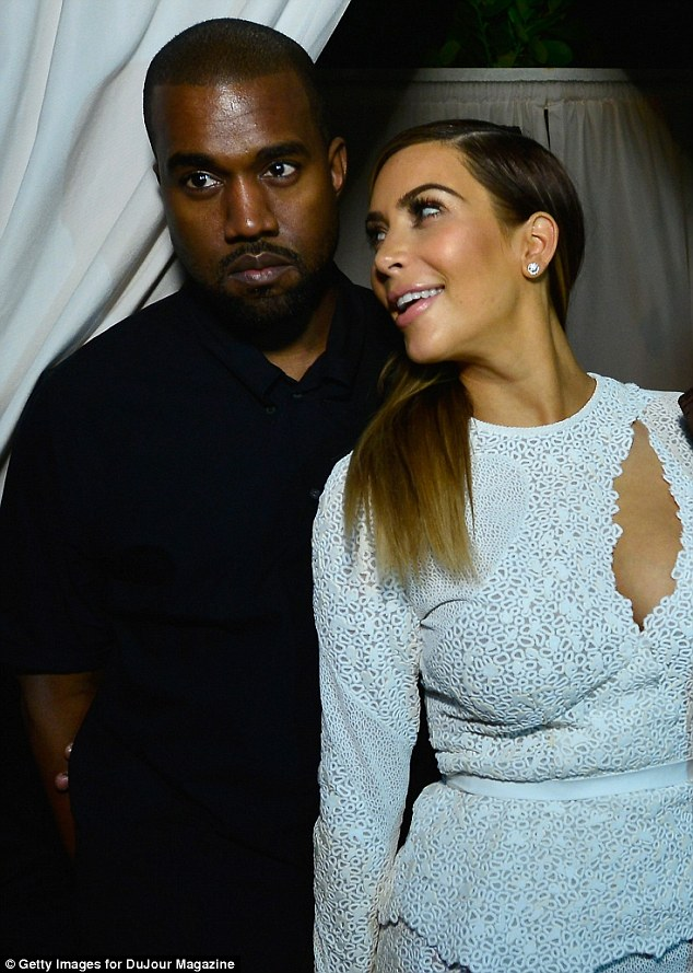 The look of love: Kim looks lovingly into Kanye's eyes as they pose for photographers