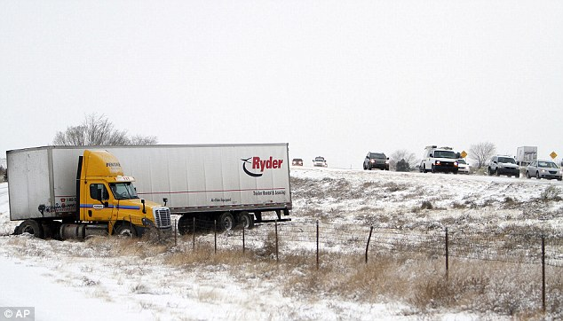 An 18-wheeler sits awaiting help after sliding off the road as traffic rumbles by in New Mexico