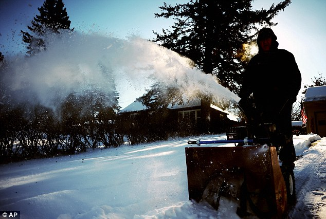 Bill Earley cleans off his driveway in Sioux Falls, South Dakota with the hose spray turning to ice as it hits the air
