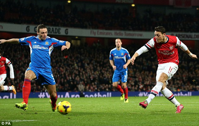 Pass and move: Arsenal's German midfielder Mesut Ozil completes an excellent team move by firing home