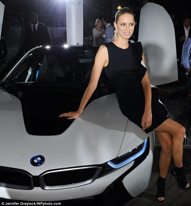 Sitting pretty: The 29-year-old looked stylish in a black and white Salvatore Ferragamo frock as she took a seat on the bonnet of the $136,000 super car