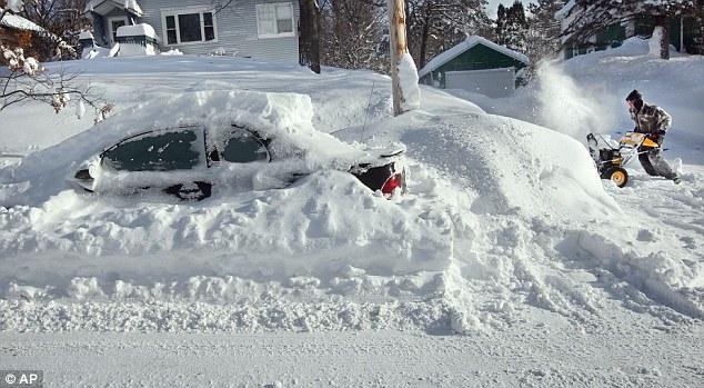 Snowed in: Scott Asperheim, of Duluth, runs his snowblower to clear the sidewalk around his home from several feet of snow Thursday