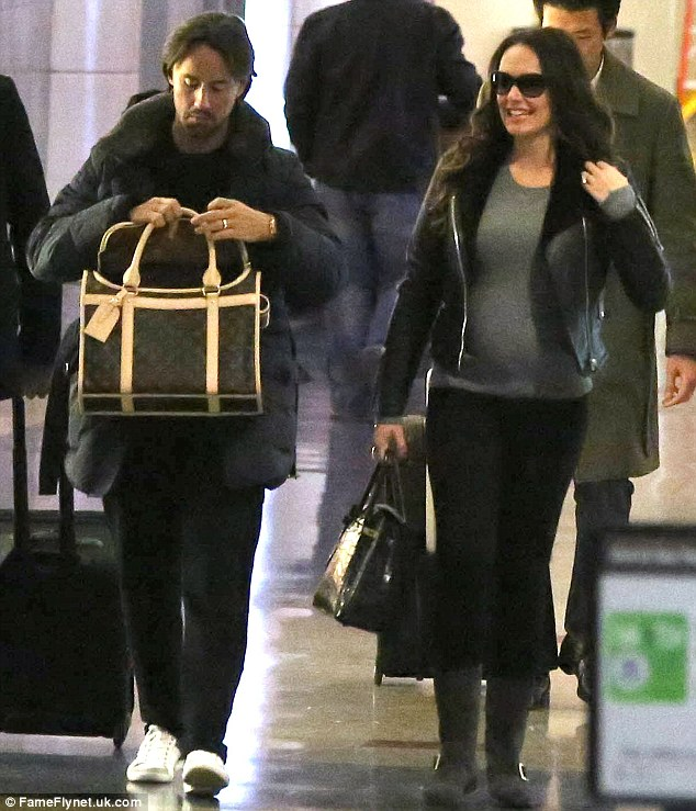 Quick check up: Jay looked in the Louis Vuitton holdall to make sure that the little dog was okay, as Tamara's bump can now be visibly seen