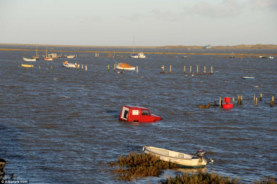 Agencies are continuing to assess the impact the flood waters have had on homes, businesses and flood defences as they prepare for the risk of further flooding today. Pictured is The Quay  car park, at Morston, on the north Norfolk coast