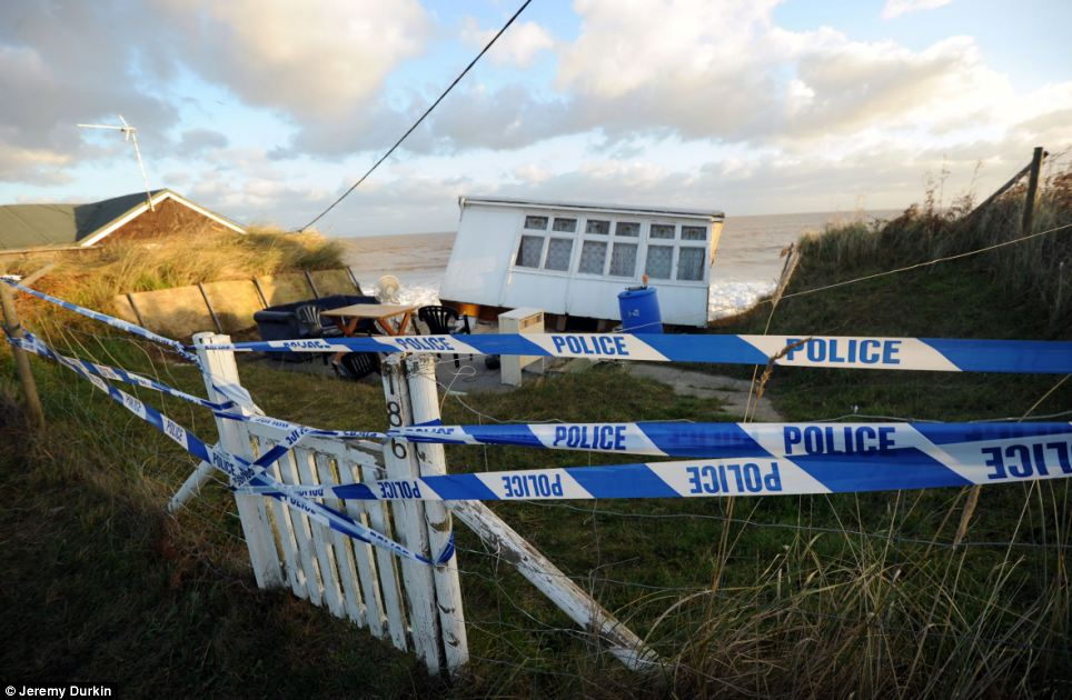 Police have cordoned off one of the bungalows which has fallen into the sea after cliffs at Hemsby collapsed