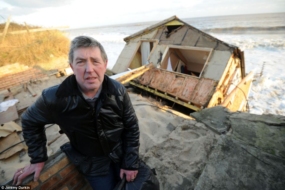 Owner Steve Connelly assesses what is left of his home after it fell into the North Sea during the storms on Thursday night