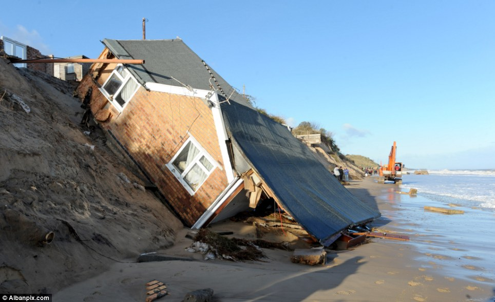 The scene on Friday: Steven and Jackie Connelly's home in Hemsby, Norfolk, slid down the cliff moments after they rescued their cats and a few possessions
