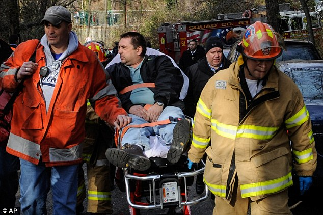 Suspended: Train driver William Rockefeller is wheeled on a stretcher away from the area where the commuter train he was operating derailed in the Bronx borough of New York
