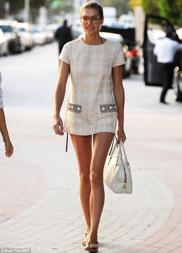 Long and lean: The model showcased her pins in the cream cover-up, which she paired with tan sandals