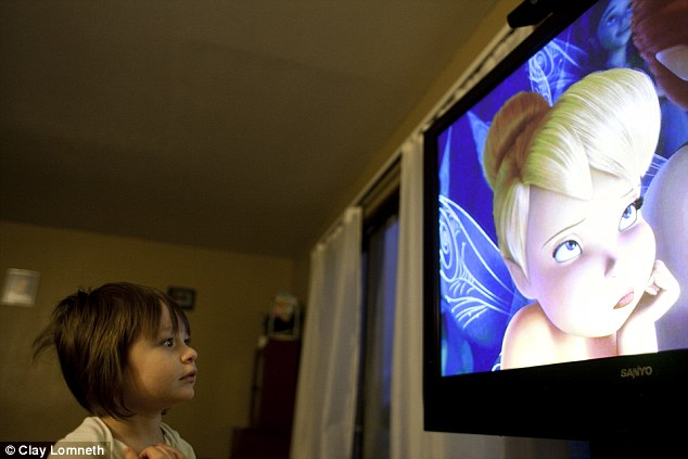 Fascinated, Michaelynn watches a Tinkerbell movie at the family's old apartment