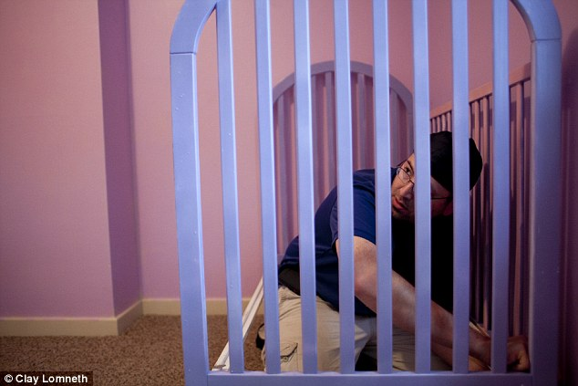 Moving day: Trevor sets up a crib in his daughter's new room after they move home