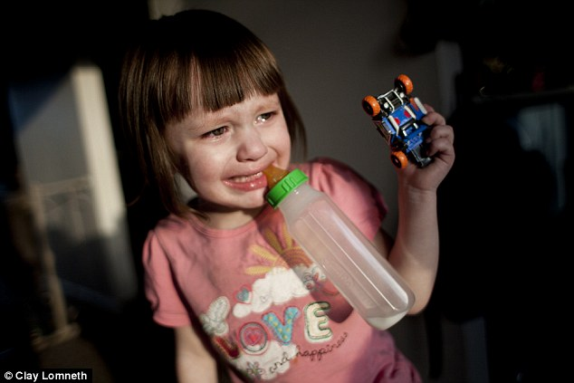 A distressed Michaelynn cries as she clings to a toy car