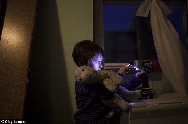The inquisitive three-year-old shines a light on her face as she plays at night