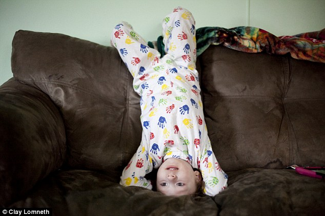Michaelynn watches TV upside down. Often when she is upset her parents hold her by her feet to help calm her