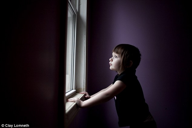 Michaelynn looks out of her bedroom window. Her mother says she often wonders what her daughter is seeing