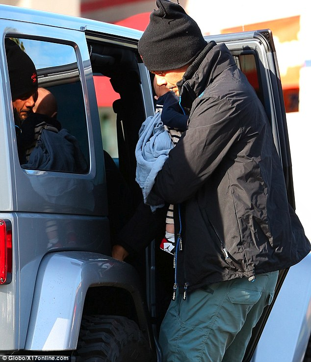 Bonding with baby: The new dad took his time as he carefully secured Axl into his car seat
