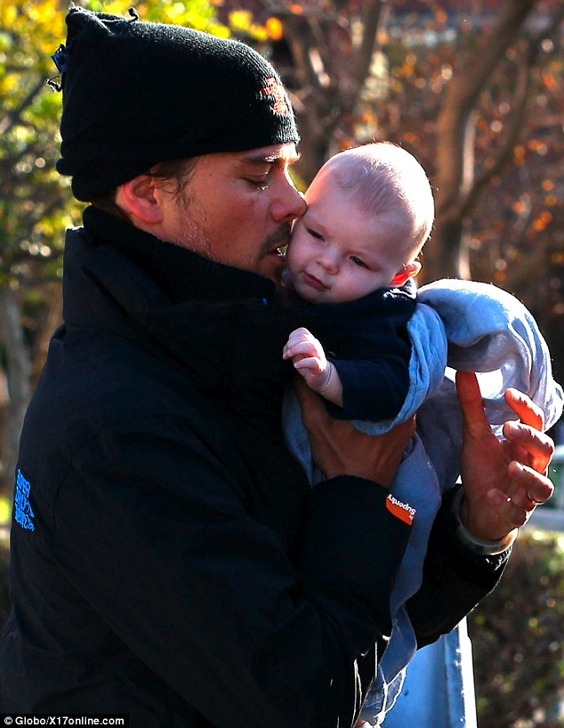 Tender touch: Josh Duhamel gives his son Axl a sweet kiss after lifting him from his baby seat during a shopping trip in Brentwood, California on Sunday