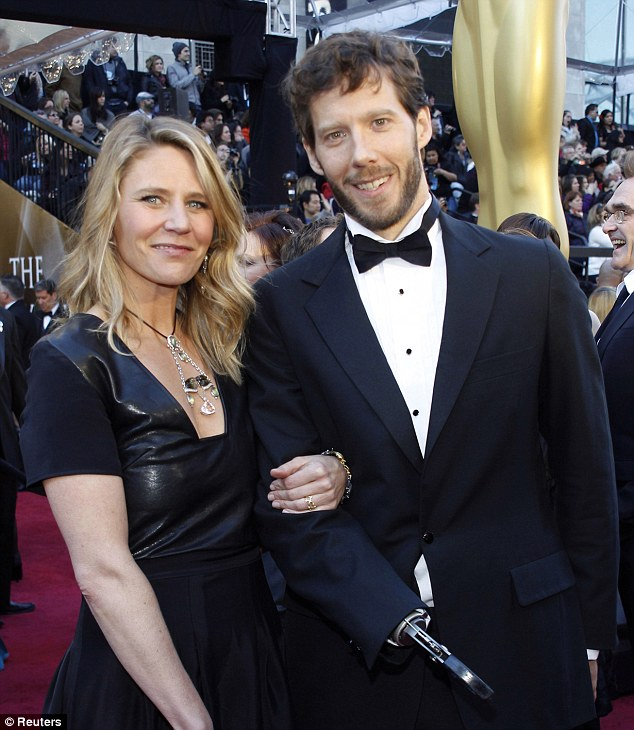 Booked: Aron Ralston, 38, left, faces two charges after he was arrested for domestic violence on Saturday. He is pictured at the Academy Awards in 2011 with wife Jessica Trusty