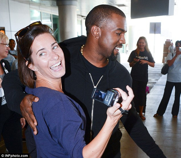 Friends again: Kanye West apologises to photographer Logan Fazio after a clash at Miami International Airport